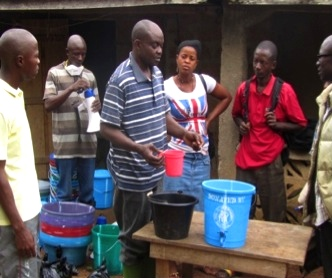 DHMT staff teaches Community Sensitisation Committee members chlorine mixture.